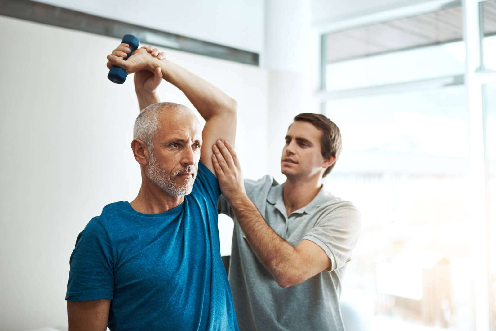 A man doing arm exercises with a physiotherapist