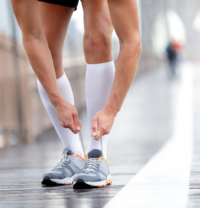 A man wearing compression socks and lacing up his athletic shoes.