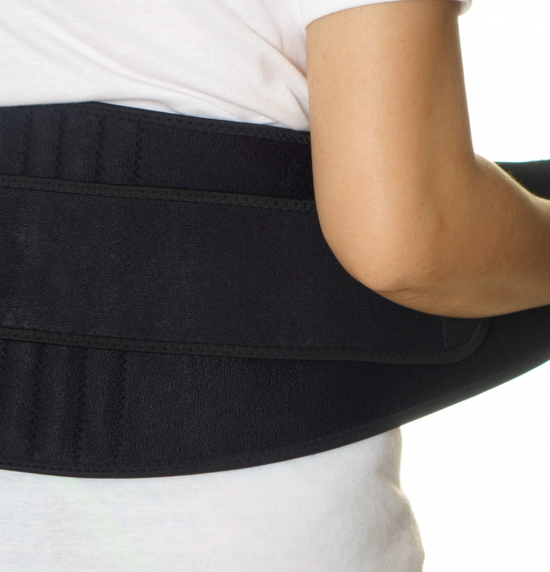 A patient putting on a lower back brace.