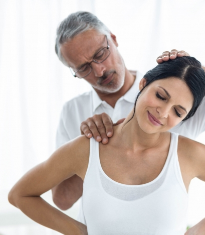 A physiotherapist performs an assisted neck stretch on a patient.