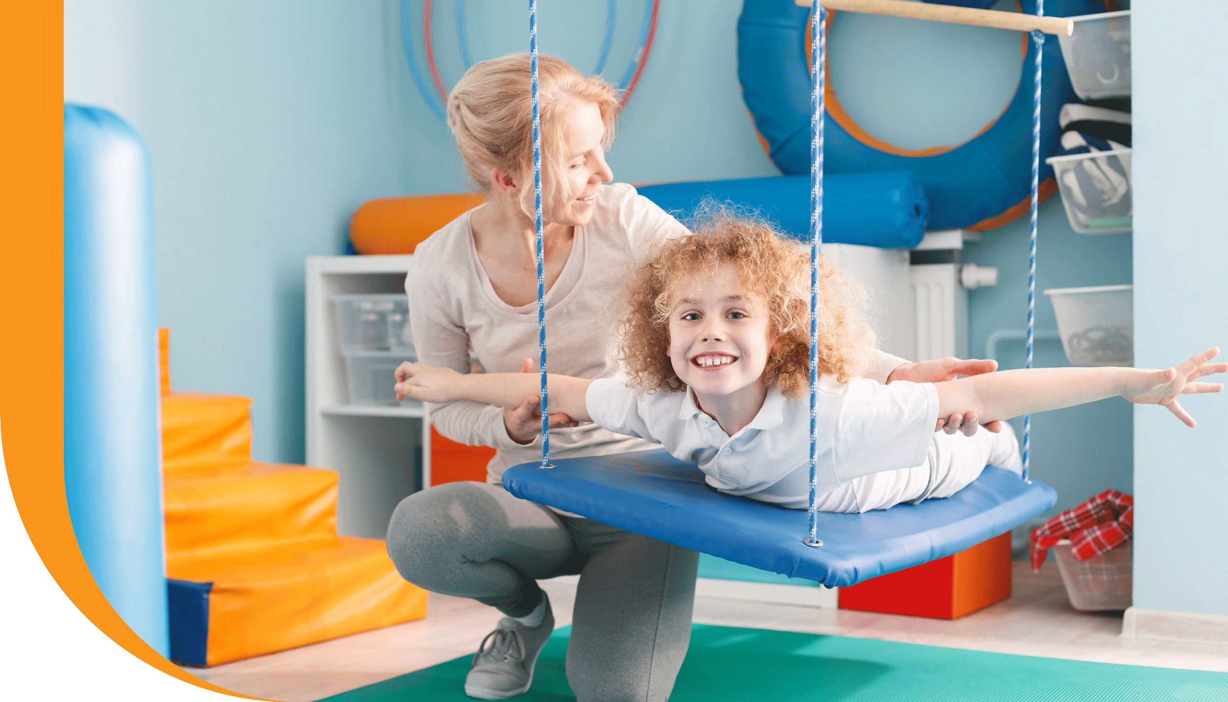 A physiotherapist guides a child through a balancing exercise.